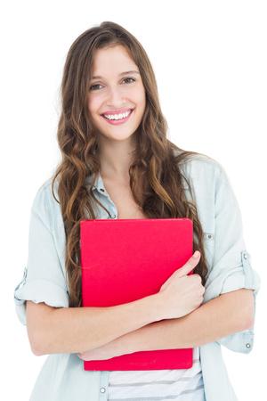 白い背景の上の本を保持している女性学生の肖像画 写真素材