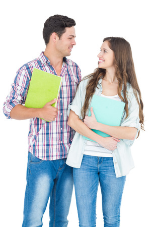 Portrait of students couple holding books on white background