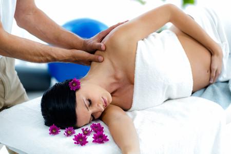 Schwangere Frau mit einer Rückenmassage von Masseur auf Wellness Empfang Lizenzfreie Bilder