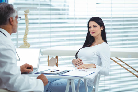 obstetrician: Pregnant woman interacting with doctor at clinic during health checkup Stock Photo