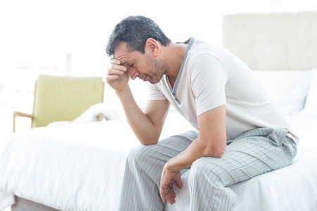 hand on forehead: Worried man sitting on bed with hand on forehead