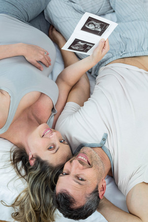 sonography: Expecting couple lying on bed and looking sonography reports