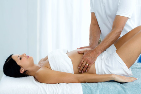 relax massage: Pregnant woman receiving a stomach massage from masseur at home