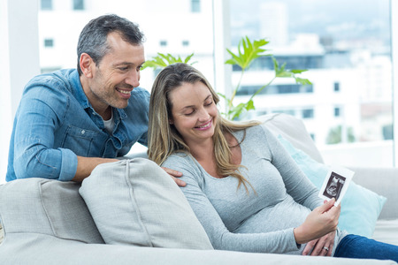 ultrasound scan: Couple sitting on sofa and looking at ultrasound scan