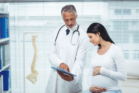 interacting: Pregnant woman interacting with doctor in clinic