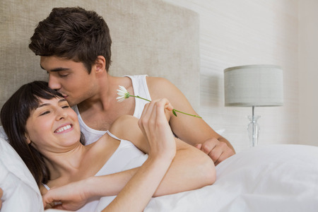 young couple kiss: Man kissing woman on forehead while offering a flower in bedroom