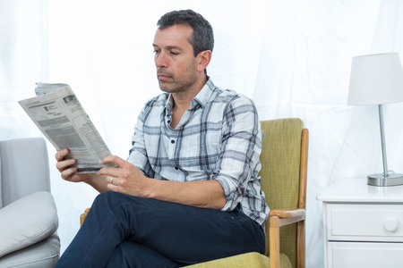 news paper: Man sitting on a chair and reading news paper