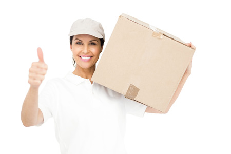 workwoman: Delivery woman carrying a package and showing thumbs up on white background Stock Photo