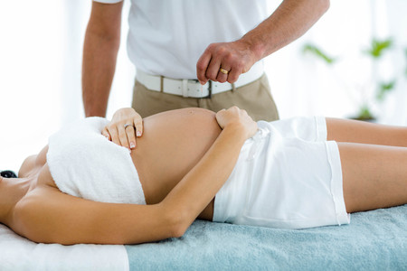 masseur: Pregnant woman receiving a spa treatment from masseur at home Stock Photo