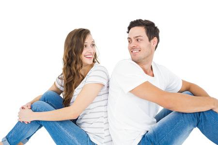 femme romantique: Jeune couple assis sur le plancher dos à dos sur fond blanc
