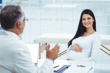 Pregnant woman interacting with doctor at clinic during health checkup Stock Photo