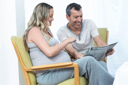 news paper: Expecting couple sitting on chair and reading news paper