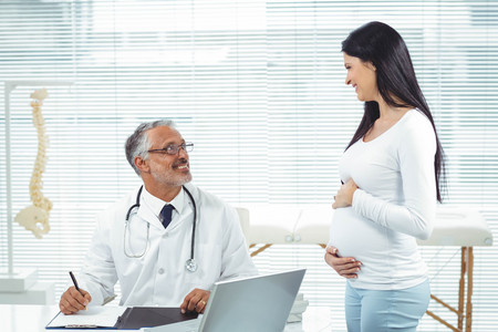 interacting: Pregnant woman interacting with doctor at clinic during health checkup Stock Photo