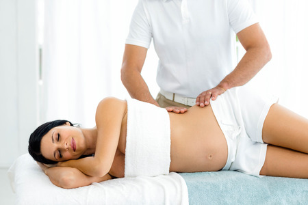 spinal conditions: Pregnant woman receiving a back massage from masseur at home