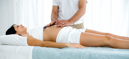 masseur: Pregnant woman receiving a stomach massage from masseur at home