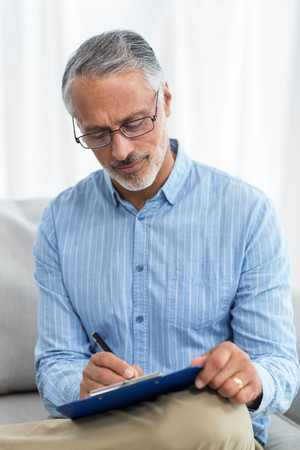 obstetrician: Doctor writing on a clipboard at home
