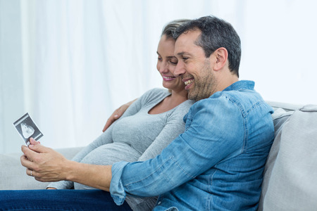ultrasound: Couple sitting on sofa and looking at ultrasound scan