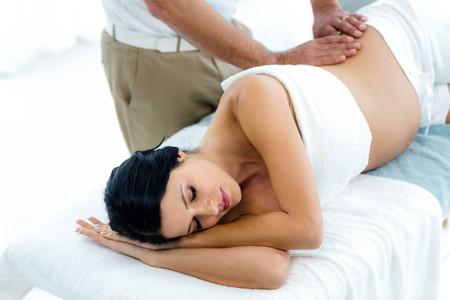 Těhotná žena obdrží masáž zad od maséra doma Reklamní fotografie