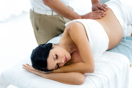 Une femme enceinte recevant un massage du dos de masseur à la maison