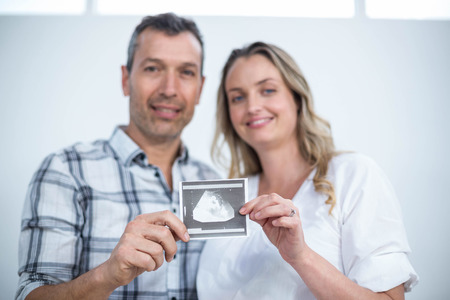 sonography: Portrait of pregnant couple holding sonography report at home