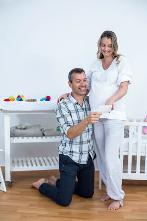 sonography: Pregnant couple holding sonography report at home Stock Photo