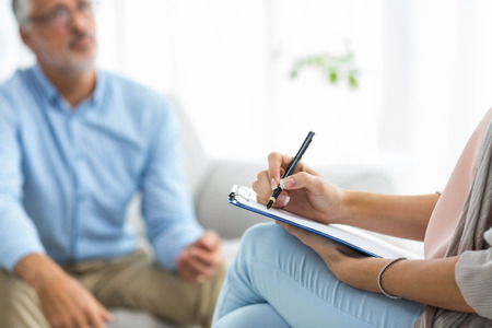 Female doctor writing on clipboard while consulting a man at home