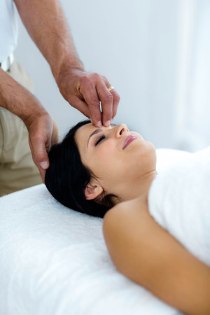 masseur: Pregnant woman receiving a head massage from masseur at home Stock Photo