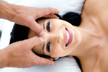 Pregnant woman receiving a head massage from masseur at home Stock Photo