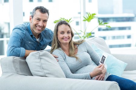 ultrasound scan: Portrait of couple sitting on sofa and holding ultrasound scan