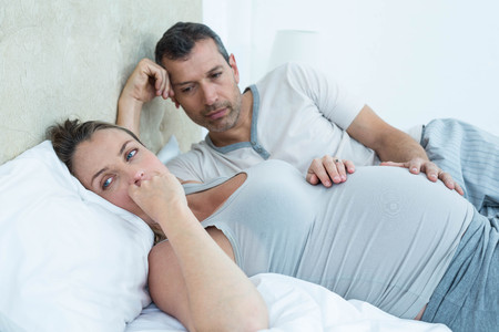gestation: Expecting couple lying on bed and chatting in their bedroom