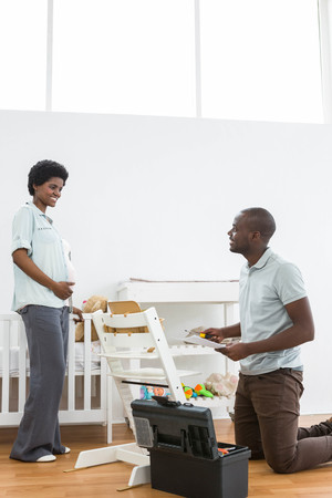 baby chair: Pregnant woman looking at man fixing a baby chair at home Stock Photo