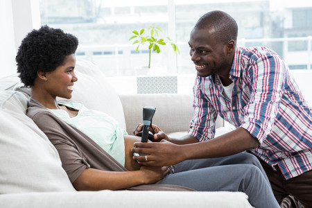 head phones: Man holding head phones on pregnant womans stomach in living room