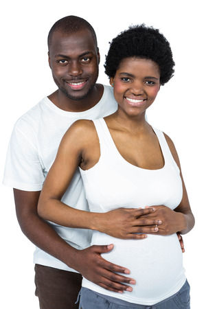 gestation: Man hugging pregnant woman from behind on white background