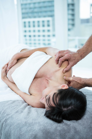 spinal conditions: Pregnant woman receiving a back massage from masseur at the health spa Stock Photo