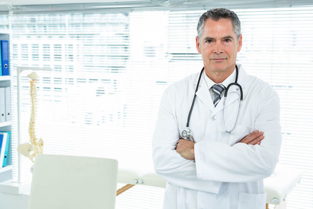 obstetrician: Portrait of confident doctor standing with his arms crossed Stock Photo
