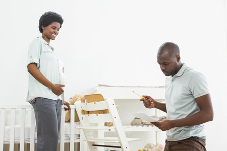 baby chair: Pregnant woman looking at man reading a list while fixing a baby chair at home Stock Photo