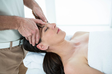 Pregnant woman receiving a face massage from masseur at the health spa