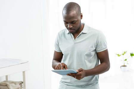 the thoughtful: Thoughtful man using a digital tablet at home Stock Photo