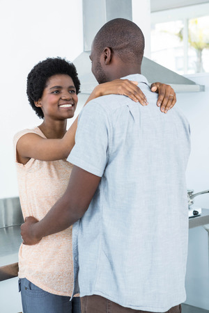 each other: Pregnant couple cuddling each other in kitchen at home