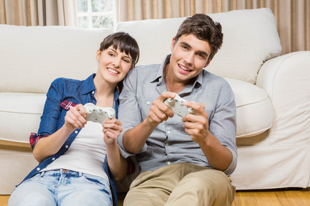 xbox: Couple playing video game in their living room Stock Photo