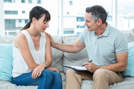 consoling: Therapist consoling a woman in the clinic