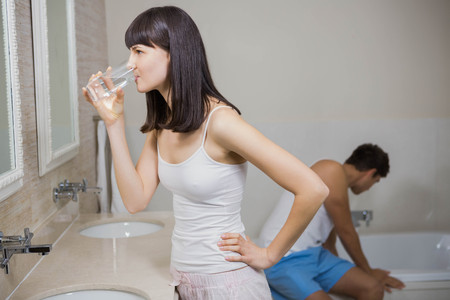 bath supplement: Beautiful woman having glass of water with medicine and man brushing teeth Stock Photo