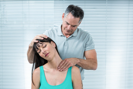physiotherapist: Physiotherapist checking pregnant womans neck in clinic