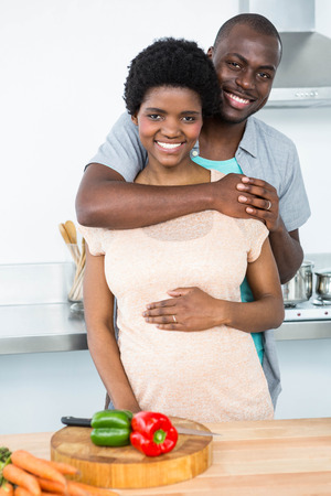 each other: Portrait of pregnant couple embracing each other in kitchen at home