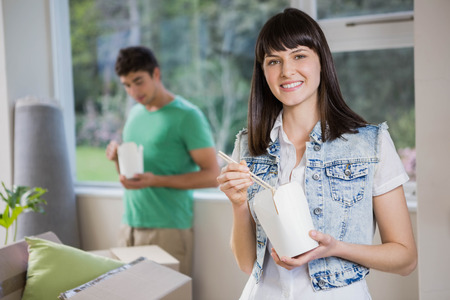 eating noodles: Smiling young woman and man eating noodles at home Stock Photo