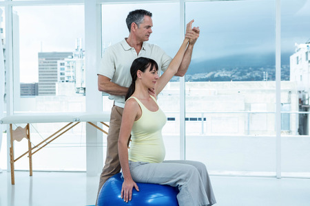 gestation: Pregnant woman exercising with physiotherapist on exercise ball at home Stock Photo