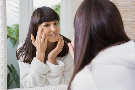 woman mirror: Beautiful young woman wearing white bathrobe looking in the mirror