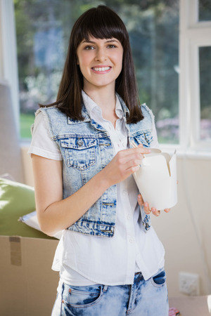eating noodles: Portrait of a smiling young woman eating noodles at home Stock Photo