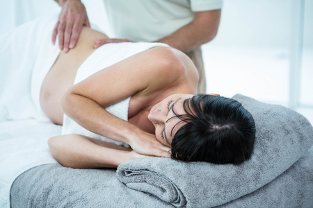 back sprains: Pregnant woman receiving a back massage from masseur at the health spa Stock Photo