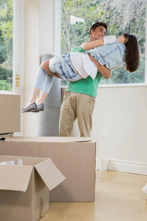 standing together: Young man lifting woman in his arms  while unpacking carton boxes in new house
